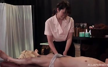 Big natural special Japanese pleasures him with a massage and a titjob