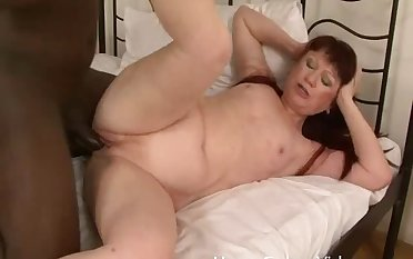 Mature redhead moans with pleasure while a black man drills her