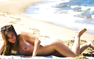 Petite body MILF Lily Chey suntanning aloft the beach